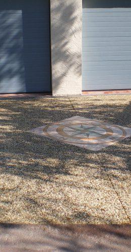Entrée de garage en béton désactivé avec intégration d'une rose des vents en béton empreinte